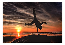 One handed hand stand at sunset on beach