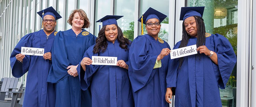 Graduation photo of students holding signs in caps and gowns.