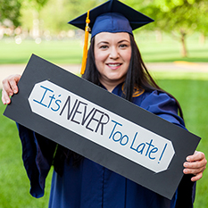 "Graduate holding a sign reading ""It's NEVER too late!"""